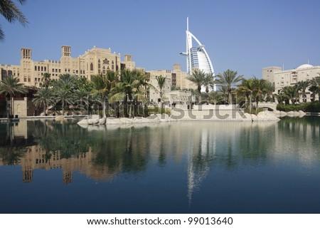 Madinat Jumeirah and the Tower of Arabs (Burj Al Arab) in Dubai reflecting in an artificial pool. - stock photo