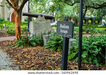 Madison Square park in downtown Savannah, Georgia with canon in the background. - stock photo