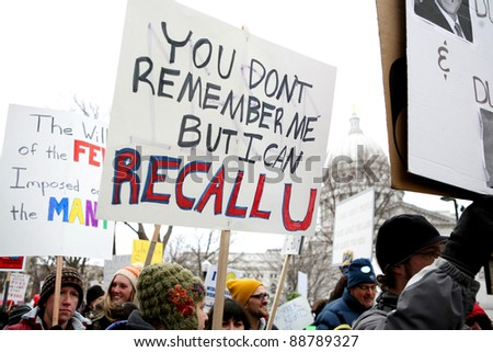 MADISON,WI - FEB 19: Signs are lifted in front of Wisconsin's Capitol protesting Gov Scott Walker on Feb 19, 2011 in Madison, WI.  The Wisconsin drive to recall Walker starts Nov 15. - stock photo