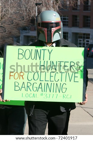 MADISON, WI - FEB 19: Unidentified man protests WI Budget Repair Bill on February 19, 2011 in Madison, WI.  The man wears a Boba Fett helmet costume and holds a sign in support of union workers. - stock photo