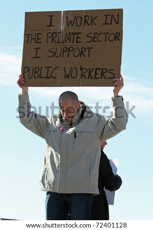 MADISON, WI - FEB 19: Unidentified man protests WI Budget Repair Bill on February 19, 2011 on the capitol square in Madison, WI.  The man holds a sign in support of public workers.