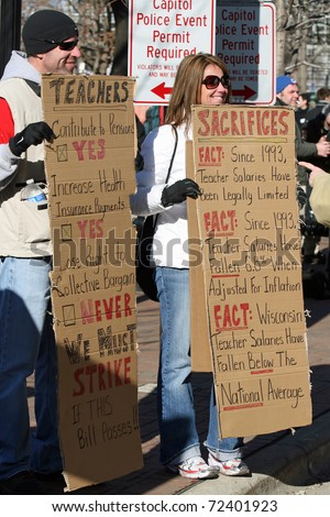 MADISON, WI - FEB 19: Unidentified people protest WI Budget Repair Bill on February 19, 2011 on the capitol square in Madison, WI.  The protesters hold signs supporting public school teachers.
