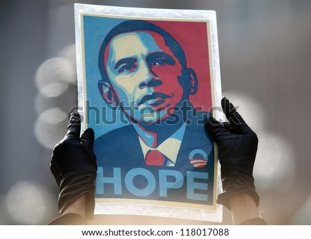 MADISON,WI-NOV. 5:A supporter holds the iconic poster of Barack Obama by Sheppard Fairey aloft at an Obama rally held the day before the 2012 election in Madison, Wisconsin on November 5, 2012. - stock photo