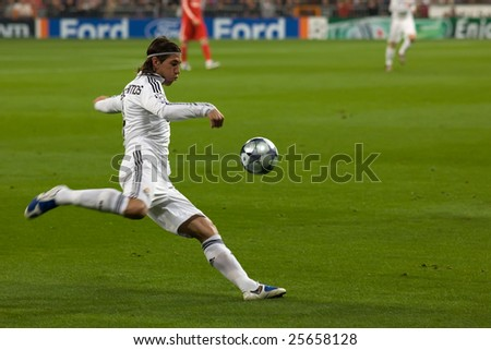 MADRID - FEB 25: Real Madrid player Sergio Ramos crosses a ball during their Champions League second round match against Liverpool FC on February 25, 2009 in Madrid. - stock photo