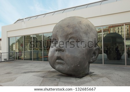 MADRID - MARCH 2:Baby sculpture by Antonio Lopez at Puerta de Atocha Railway Station on March 2, 2013 in Madrid, Spain