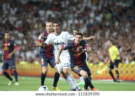 MADRID, SPAIN - AUGUST 29: Leo Messi fights for the ball with Angel Di Maria during the Supercopa, Real Madrid vs FC Barcelona, on August 29, 2012 at the Santiago Bernabeu Stadium. - stock photo
