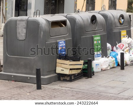 MADRID, SPAIN - DECEMBER 27, 2014: containers for recycling on the street surrounded by trash. - stock photo