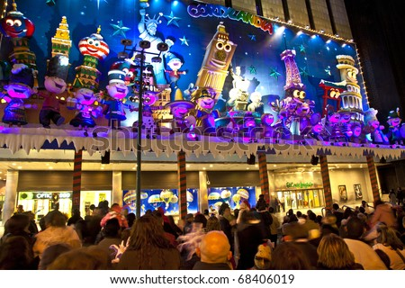 MADRID, SPAIN - DECEMBER 20: People have fun in Christmas time watching the famous puppet show and illumination at center El Corte Ingles on December 20, 2010 in Madrid, Spain. - stock photo