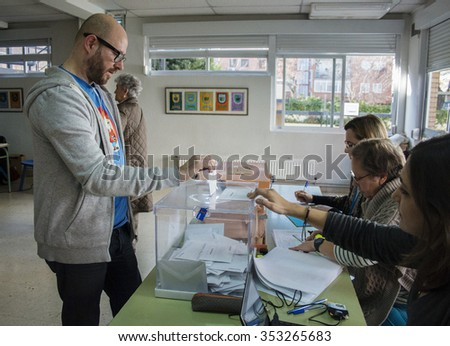 Madrid, Spain - December 20, 2015 - Voter introducing envelope inside urn at electoral college for Spanish general elections in Madrid, Spain