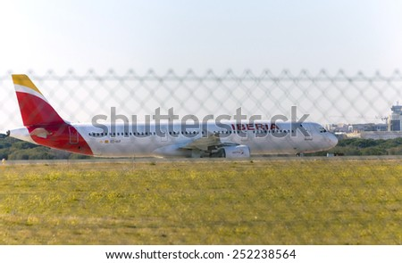 MADRID, SPAIN - FEBRUARY 08th 2015: An airplane -Airbus A321-, of the -Iberia- airline, over runway of Madrid-Barajas airport, on February 8th 2015. - stock photo