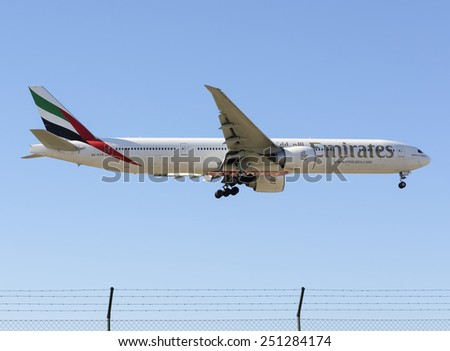 MADRID, SPAIN - FEBRUARY 08th 2015: An airplane -Boeing 777-300ER-, of the -Emirates- airline, landing on Madrid-Barajas airport, on February 8th 2015. - stock photo