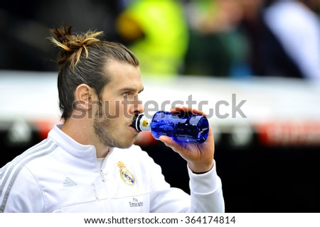 MADRID, SPAIN - January 17th, 2016:  GARETH BALE of REAL MADRID drinks water before the game during  Spanish La Liga match vs SPORTING GIJON at Santiago Bernabeu Stadium.  - stock photo