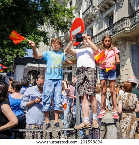 MADRID, SPAIN - JUN 19, 2014: Unidentified Spanish children with national flags in the centre of Madrid on a case the celebration on a day of the inauguration of the New King of Spain Felipe IV