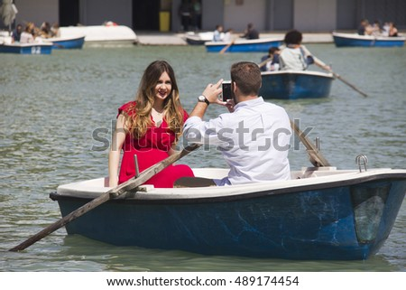 Madrid, Spain - May 29, 2016: Couple boating and taking pictures in the pond of El Retiro park in Madrid, Spain on May 29, 2016