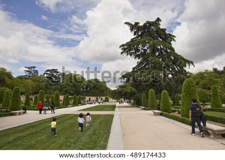 Madrid, Spain - May 29, 2016: Father and children running in the grass of El Retiro park in Madrid, Spain on May 29, 2016