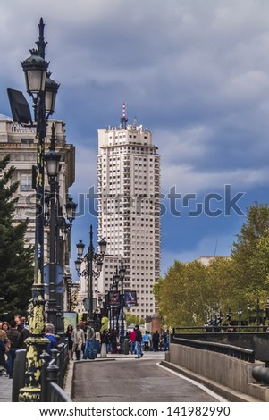 MADRID, SPAIN - MAY 15: Madrid Tower (named Madrid Tower) in downtown on May 15, 2012 in Madrid, Spain. Otamendi brothers architects, 1954 - 1960. 142 meters height. People walking on the street. - stock photo