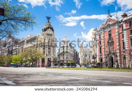 Madrid, Spain - May 6, 2012: Metropolis Building (Edificio Metropolis) and Grassy Building (Edificio Grassy) famous Beaux-Arts style of Madrid and San Jose church, Spain - stock photo