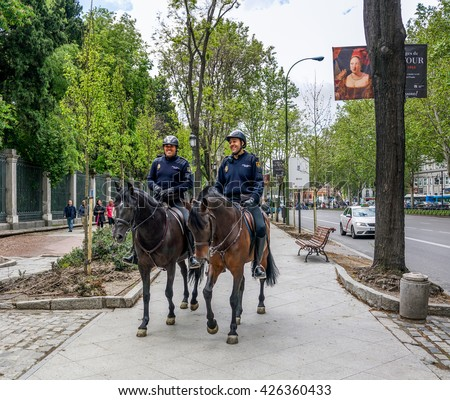 MADRID, SPAIN - MAY 12, 2016 :Smiling  police officers on horseback  at Museum Prado area in Madrid, Spain.