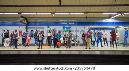 MADRID, SPAIN - MAY 28, 2014: Tube, underground station with commuters awaiting train - stock photo