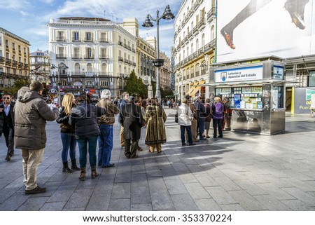 MADRID, SPAIN - November 26, 2015: typical Christmas queues to buy national lottery in the famous Puerta del Sol in Madrid, Spain - stock photo