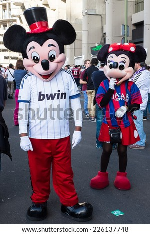 MADRID, SPAIN - OCTOBER 25, 2014: A couple of Mickey and Minnie Mouse with Real Madrid and Barcelona shirts, walking around Santiago Bernabeu Stadium at the Real Madrid-Barcelona match. - stock photo