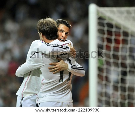 MADRID, SPAIN - October 5th, 2014 : Portuguese CRISTIANO RONALDO and GARETH BALE of Real Madrid hug each other celebrating together Ronaldos goal during La Liga match at Santiago Bernabeu Stadium.  - stock photo