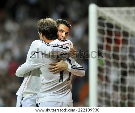 MADRID, SPAIN - October 5th, 2014 : Portuguese CRISTIANO RONALDO and GARETH BALE of Real Madrid hug each other celebrating together Ronaldos goal during La Liga match at Santiago Bernabeu Stadium.  - stock photo