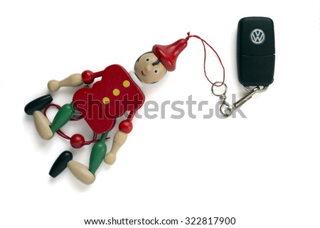MADRID, SPAIN - SEPTEMBER 30, 2015: keychain with the logo of the Volkswagen car company with a puppet Pinocchio. Isolated on white background. illustrative editorial - stock photo