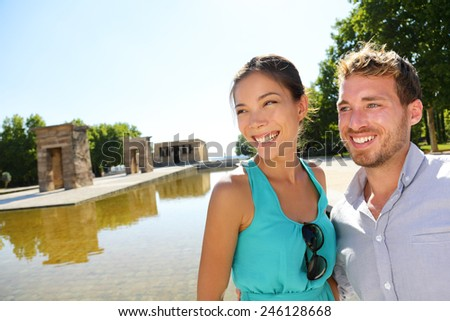 Madrid tourist couple by Temple of Debod. Tourists sightseeing in Madrid visiting tourist destinations and attractions in Madrid, Spain. Asian woman, Caucasian man. - stock photo
