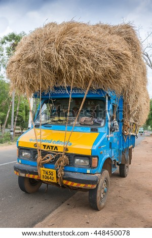 Madurai, India - October 18, 2013: A blue TATA Truck is overloaded with rice straw and parked off the road. Crew in cabin, front view. - stock photo