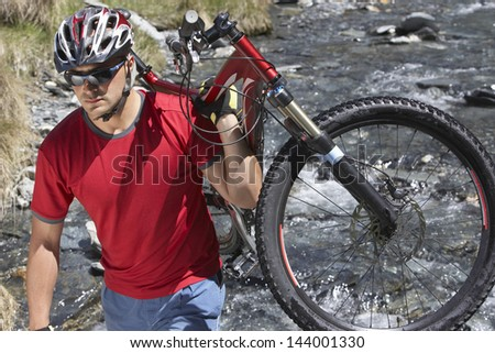 Mae cyclist in helmet carrying bike by river - stock photo