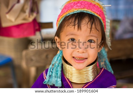 Mae Hong Son, Thailand - July 22, 2013: Karen tribe girl from the Padaung tribe poses for the camera in Mae Hong Son on July 22, 2013. Karen people wear rings on their neck from as young as five. - stock photo