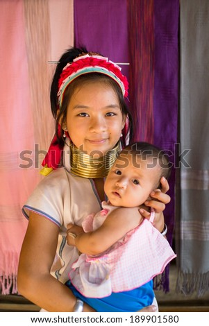 Mae Hong Son, Thailand - July 22, 2013: Karen tribe girl from the Padaung tribe poses with a baby in Mae Hong Son on July 22, 2013. Karen people wear rings on their neck from as young as five. - stock photo