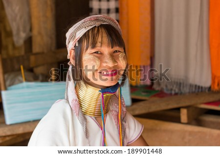 Mae Hong Son, Thailand - July 22, 2013: Karen tribe woman from the Padaung tribe poses for the camera in Mae Hong Son on July 22, 2013. Karen people wear rings on their neck from as young as five. - stock photo