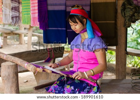 Mae Hong Son, Thailand - July 22, 2013: Karen tribe woman from the Padaung tribe weaves fabric in Mae Hong Son on July 22, 2013. Karen people wear rings on their neck from as young as five. - stock photo