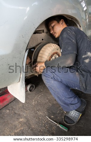 MAE SOT, THAILAND - NOV2, 2015 : Unidentified technician is repairing brake system and suspension of pickup truck at Mae Sot, Thailand on NOVEMBER2, 2015 - stock photo