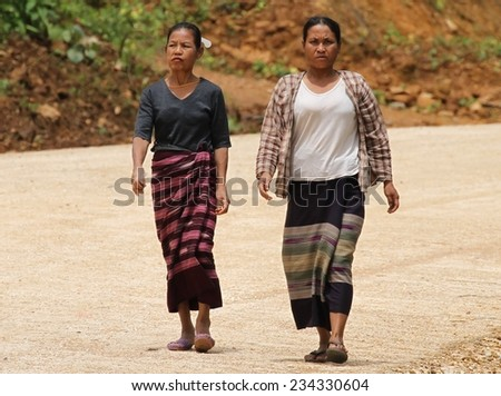 MAE SOT, THAILAND - SEPTEMBER 1: Two hill tribe women walking along the highway from Mae Sariang heading south to Mae Sot, Thailand on the 1st September, 2014.