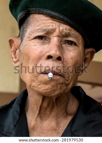 MAE TAN NOI, THAILAND - MARCH 22 2015: Elderly Thai Man, sits and smokes at remote train station Mae Tan Noi on one of the hottest recorded days in Northern Thailand. - stock photo