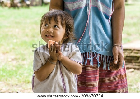 MAEHONGSON THAILAND-July 26:Unidentified girl eating cake during KAREN village meeting on July 26, 2014 in PAI, MAEHONGSON,  Thailand. PAI is a city of ethnic, well known as tourist place.