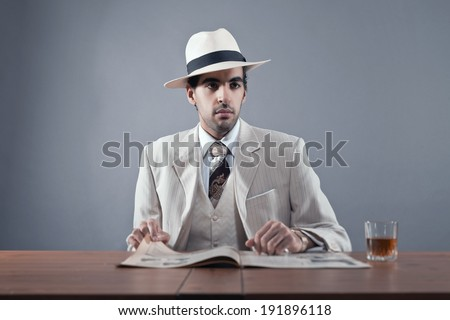 Mafia fashion man wearing white striped suit and hat. Sitting at table with glass of whisky and newspaper. Studio shot. - stock photo