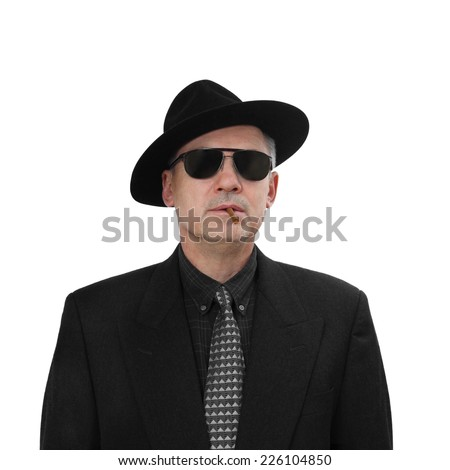 Mafia is immortal - dangerous looking middle aged man in classic black suit and hat with sunglasses smokes cigarillo isolated on white background - stock photo
