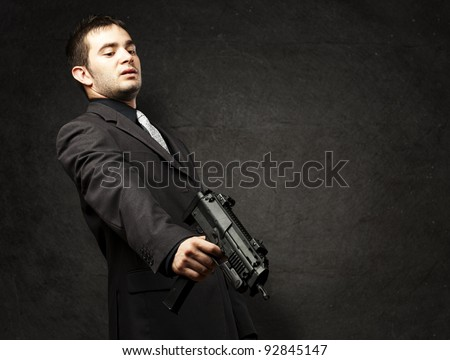mafia man aiming down with gun against a grunge wall