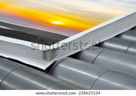 magazine binding process after offset print. Extreme closeup of the conveying process of a full-automatic binding perfect bound units. - stock photo
