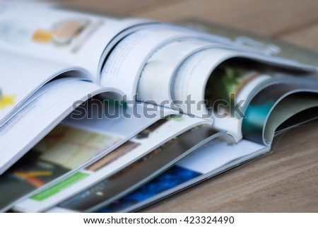 Magazine blur on a wooden table. - stock photo