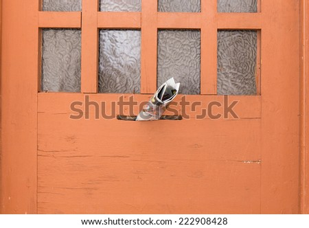 magazine in a letterbox of a wooden door. - stock photo