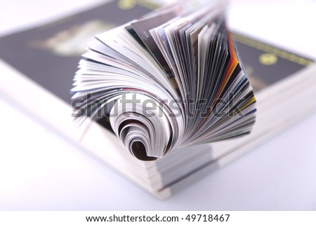 Magazine Roll isolated on white, on a bunch of other magazines - stock photo