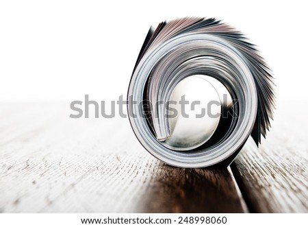 magazine roll on wooden desk - stock photo