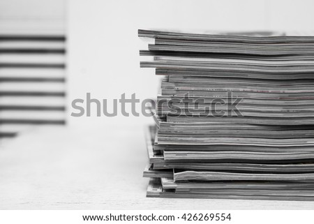 Magazine stack on white table, information concept - stock photo