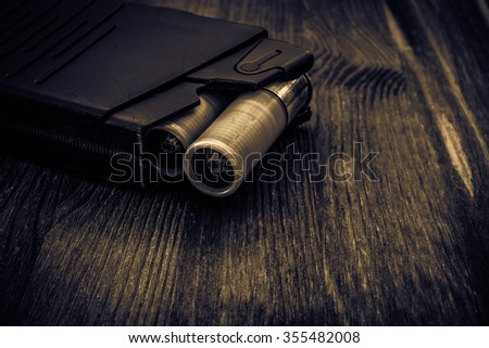 Magazine with bullet cartridges 12 gauge on the wooden table. Close up view, image vignetting and the yellow toning  - stock photo