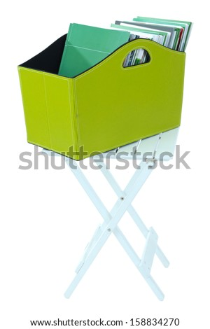 Magazines and folders in green box on table isolated on white